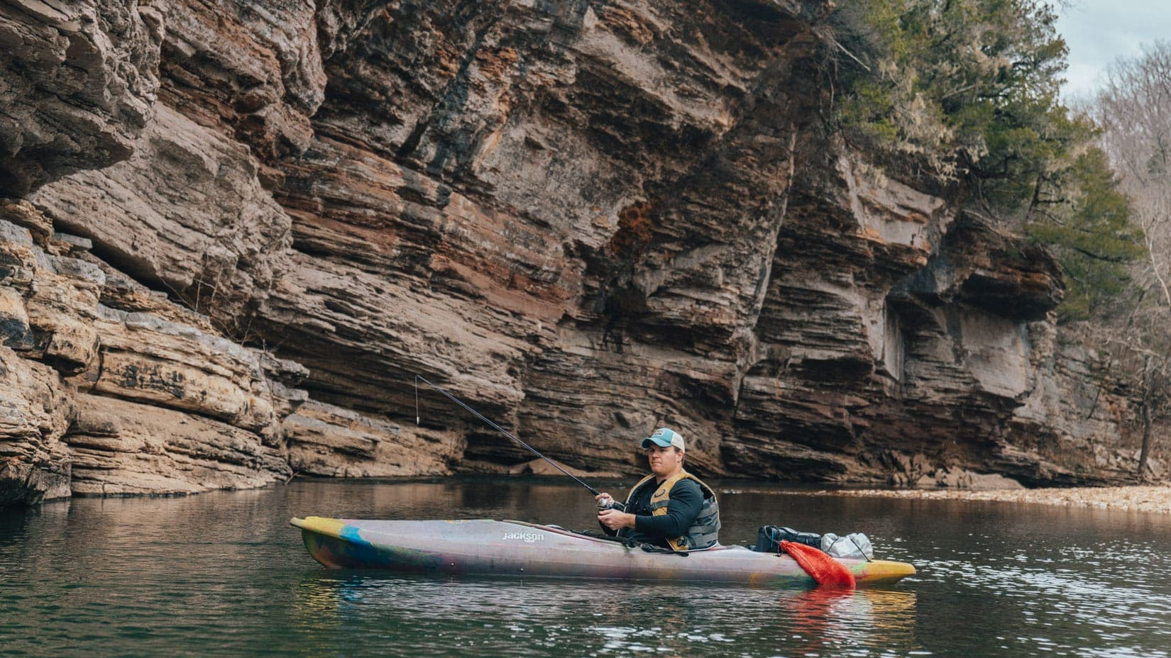 Man catching fish while kayaking